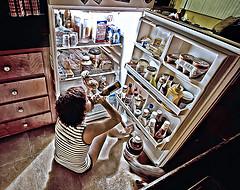 girl sitting in front of fridge