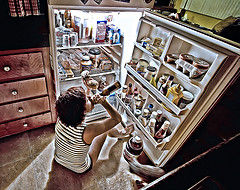 girl sitting in front of fridge