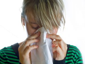 girl sneezing into tissue